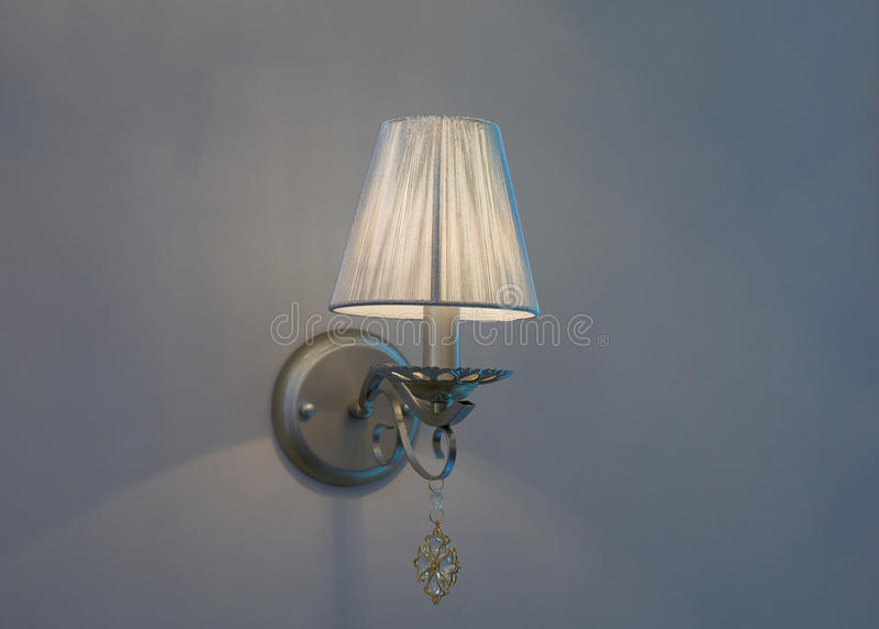 Lamp mounted on the wall. Old style switched on lamp mounted on blue wall with lampshade royalty free stock image
