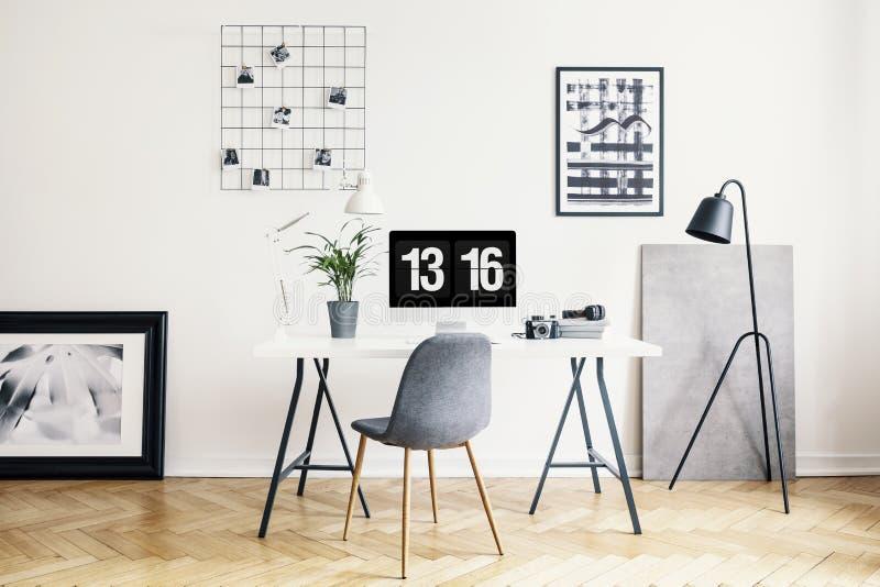 Lamp naast grijze stoel en bureau met installatie in het witte binnenland van het huisbureau met affiches Echte foto stock foto