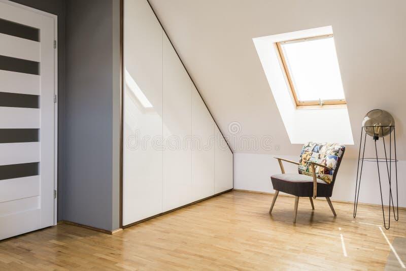 Lamp naast leunstoel op houten vloer in witte zolder binnenlandse wi royalty-vrije stock afbeelding
