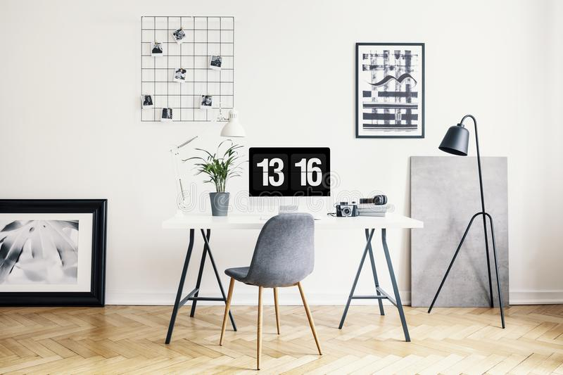 Lamp next to grey chair and desk with plant in white home office interior with posters. Real photo. Concept stock photo