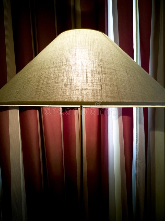 Lamp next to striped curtain royalty free stock image