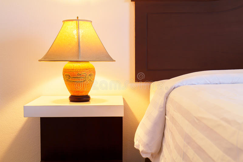 Lamp on a night table with light switched on beside the bed in. The cozy bedroom with soft gentle light royalty free stock photos