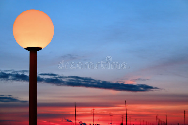 Lamp Post. Lit lamp post against sunset background royalty free stock images
