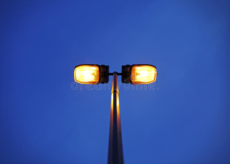 Lamp post. A solitary lit street light against a surreal evening sky for the concept of guiding light royalty free stock photo