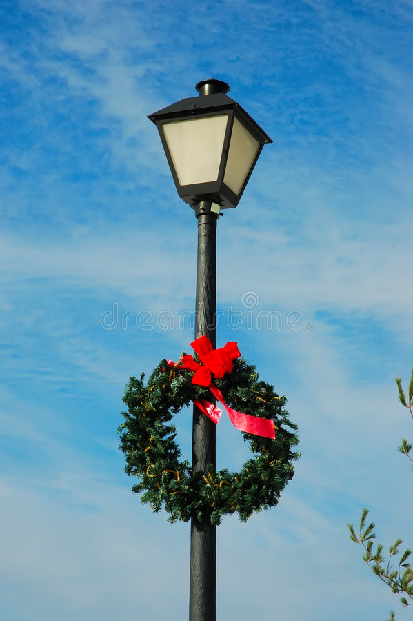 Lamp Post. With a holiday wreath against the brilliant blue of the winter sky stock photos