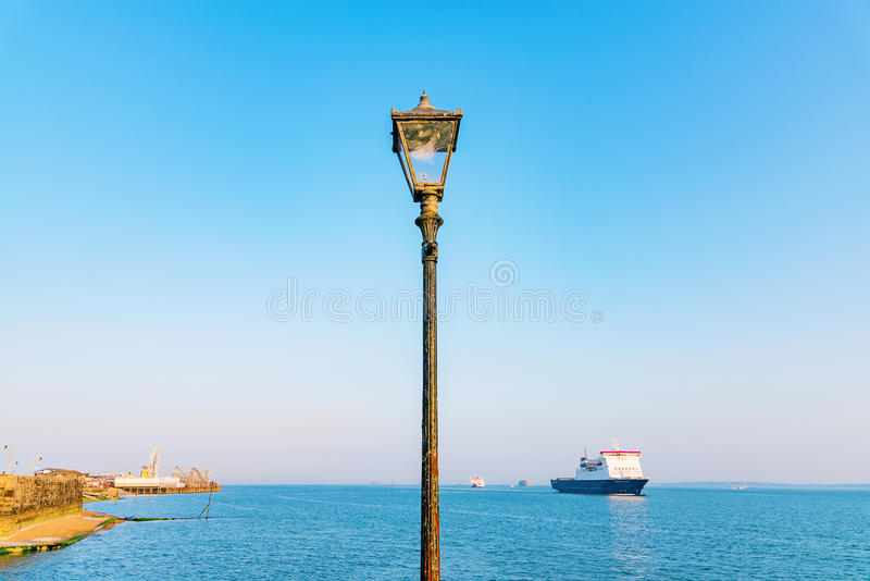 Lamp post with blue sky. Ocean and ship in the background royalty free stock images