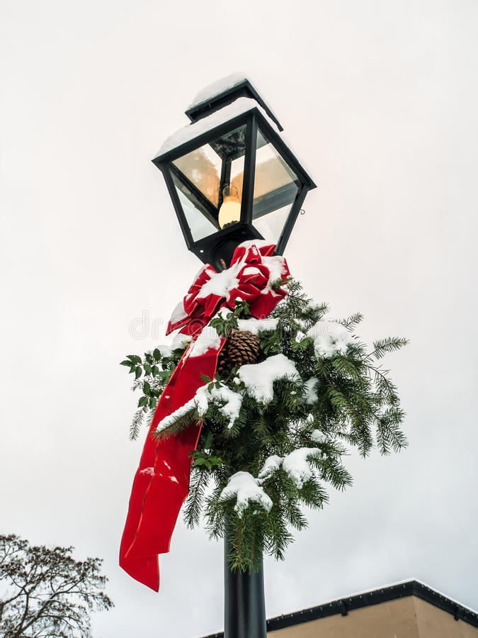 Lamp post with Christmas decoration. Old lamp post with Christmas decoration of red ribbon and evergreen bough covered with snow in Jacksonville, Oregon royalty free stock photo