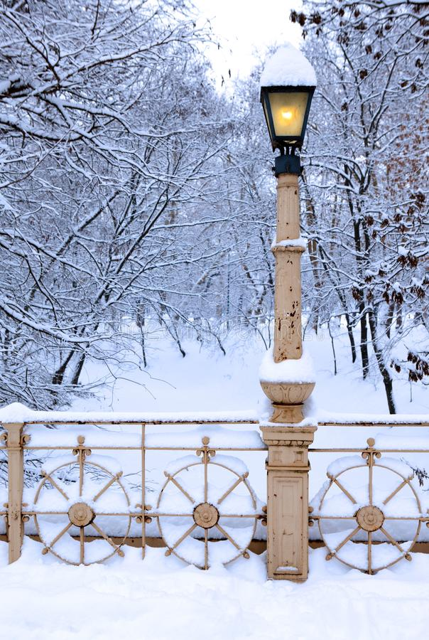 Lamp post covered by snow in park. Winter, old lamp post covered by snow in city park royalty free stock photos