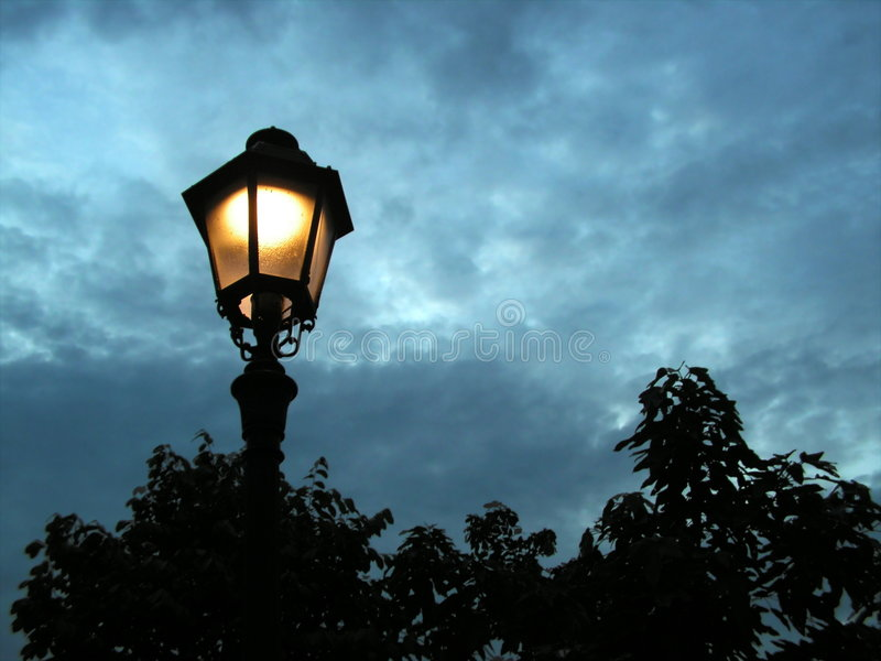 Lamp post in the evening. Lamp post at night in garden royalty free stock image