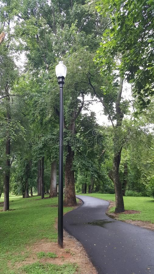 Lamp Post along Path in Park. Lamp post on path winding through park in the center of Ellijay Georgia along the river stock photo
