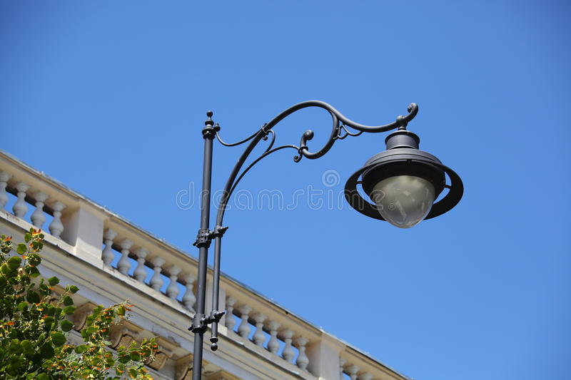 Lamp post. Vintage lamp post and an old balcony behind, on a blue sky royalty free stock photography