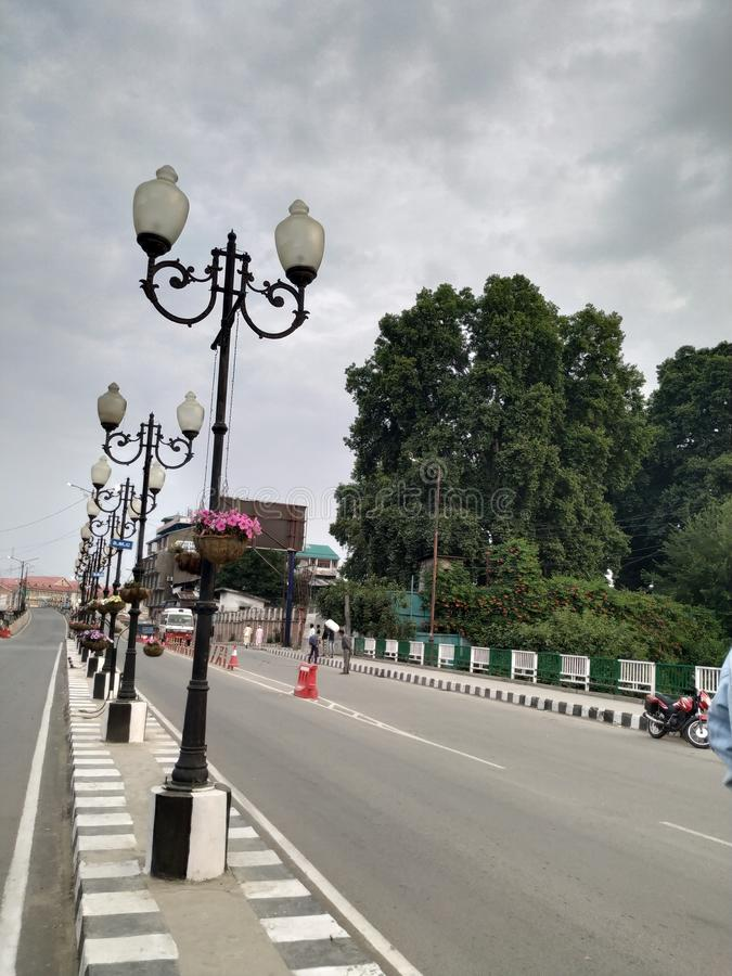 Lamp posts in row. Empty street on a cloudy day in Srinagar. The lampposts on the left side of the frame standing in a row as if reaching the skies and on the stock photo
