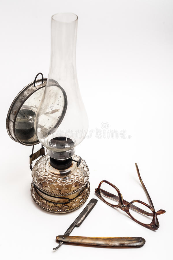 Lamp and razor. Old and worn rusty razor, oil lamp, glasses on a white background royalty free stock photo