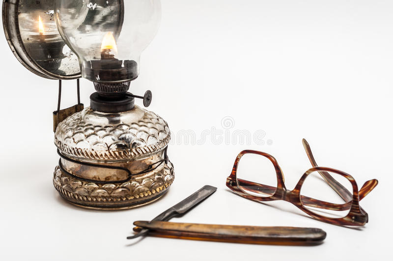 Lamp and razor. Old and worn rusty razor, oil lamp, glasses on a white background royalty free stock photos