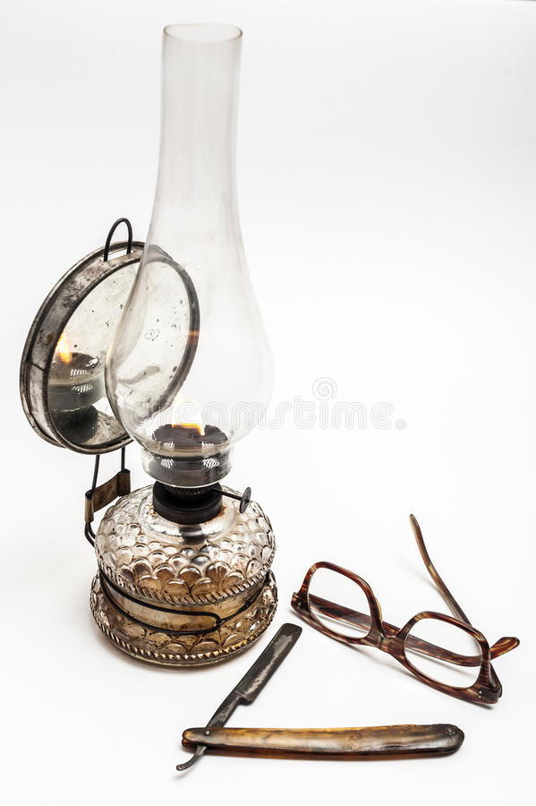 Lamp and razor. Old and worn rusty razor, oil lamp, glasses on a white background stock photo