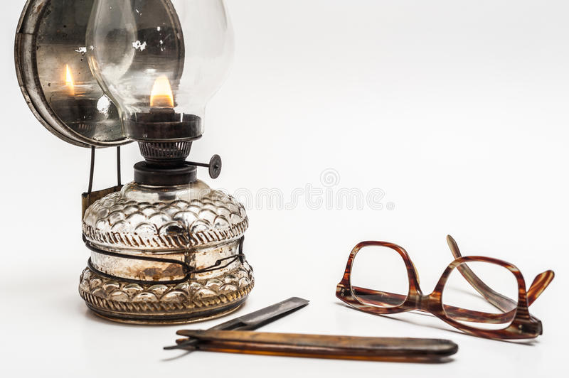 Lamp and razor. Old and worn rusty razor, oil lamp, glasses on a white background stock image