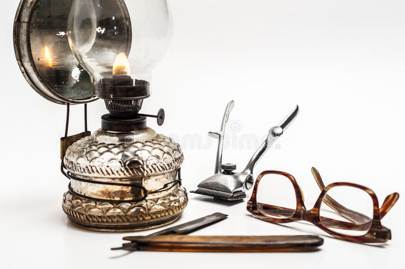 Lamp and razor. Old and worn rusty razor, oil lamp, metal trimmer and glasses on a white background stock image