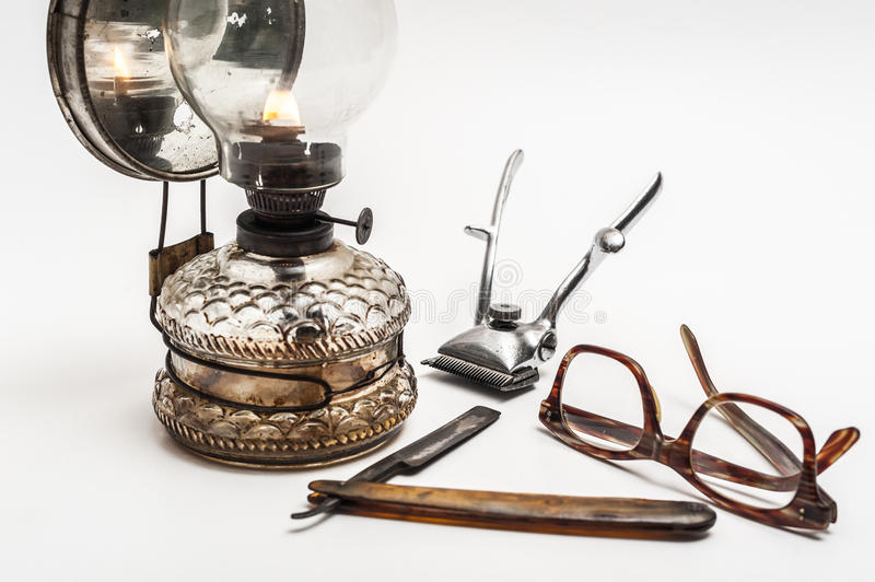 Lamp and razor. Old and worn rusty razor, oil lamp, metal trimmer and glasses on a white background stock photos