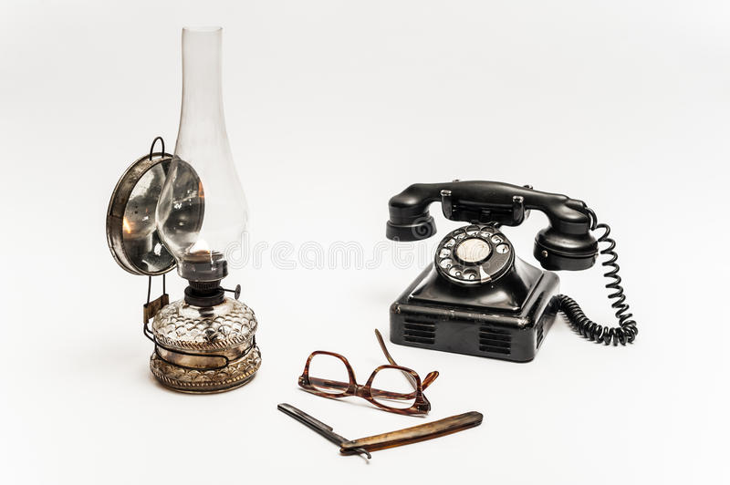Lamp and razor. Old and worn rusty razor, oil lamp, old telephone and glasses on a white background royalty free stock images