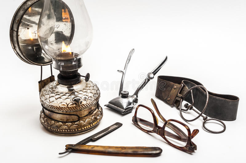 Lamp and razor. Old and worn rusty razor, oil lamp, metal trimmer and glasses on a white background royalty free stock photos