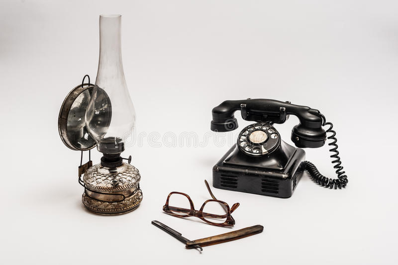 Lamp and razor. Old and worn rusty razor, oil lamp, old telephone and glasses on a white background royalty free stock image