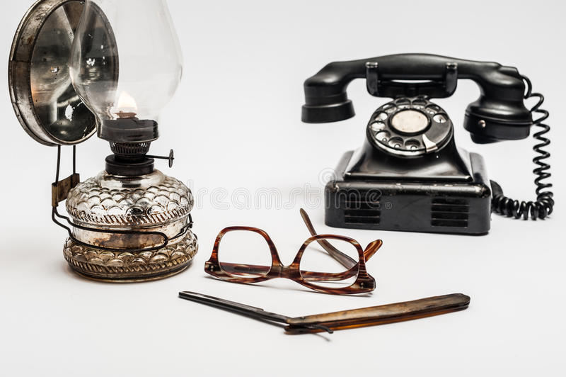 Lamp and razor. Old and worn rusty razor, oil lamp, old telephone and glasses on a white background royalty free stock photos