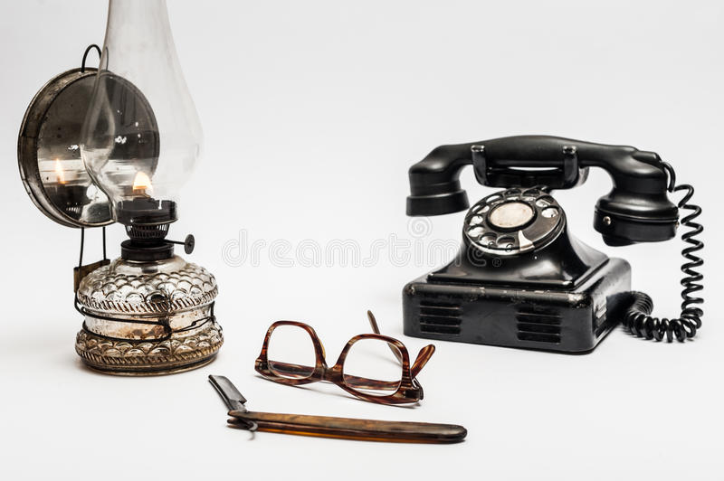 Lamp and razor. Old and worn rusty razor, oil lamp, old telephone and glasses on a white background stock photos