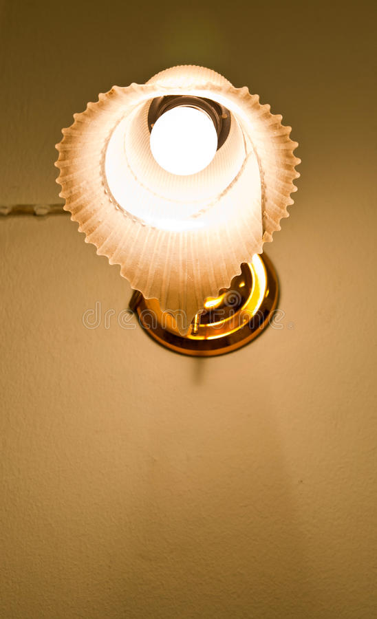 The lamp on the wall. Opened lamp on the wall in the dark room stock image