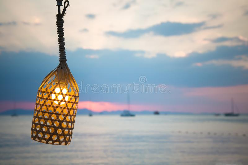The lamp on the wire tied with a rope. On the background of the beach. Inside the light bulb shines, evening.  stock image