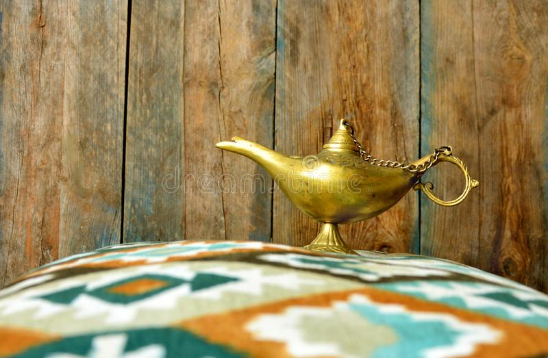 Lamp of wishes in a hand. Vintage alladin lamp background royalty free stock photography
