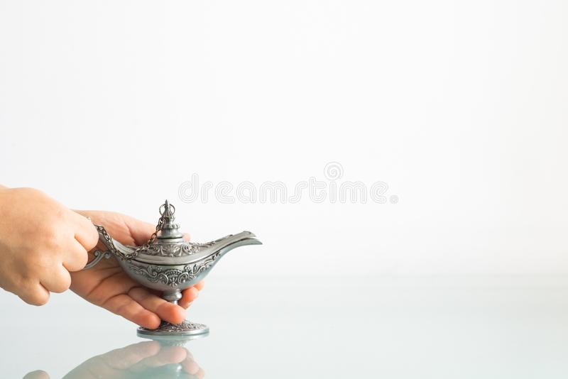 Lamp of wishes in little girl`s hands with white background royalty free stock images