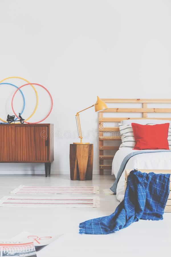 Lamp on wooden stool next to bed with red cushion and blue blanket in bedroom interior. Real photo. Concept stock image