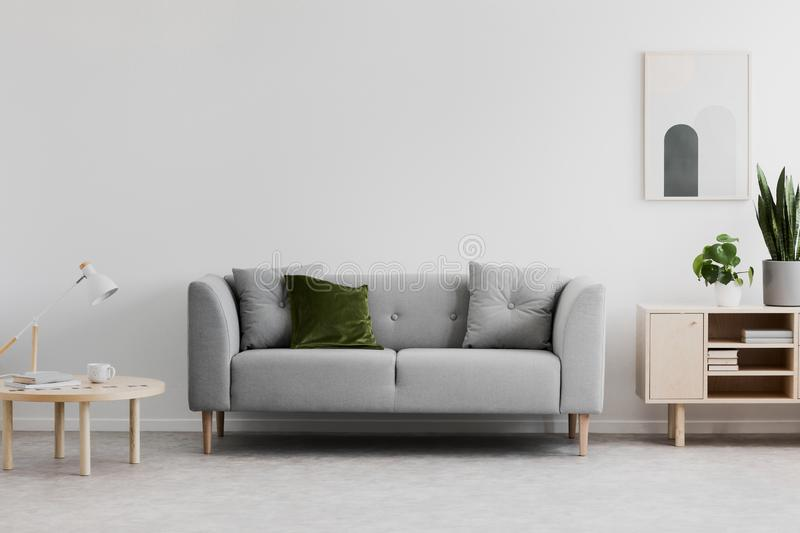 Lamp on wooden table next to grey couch in white living room int stock photo