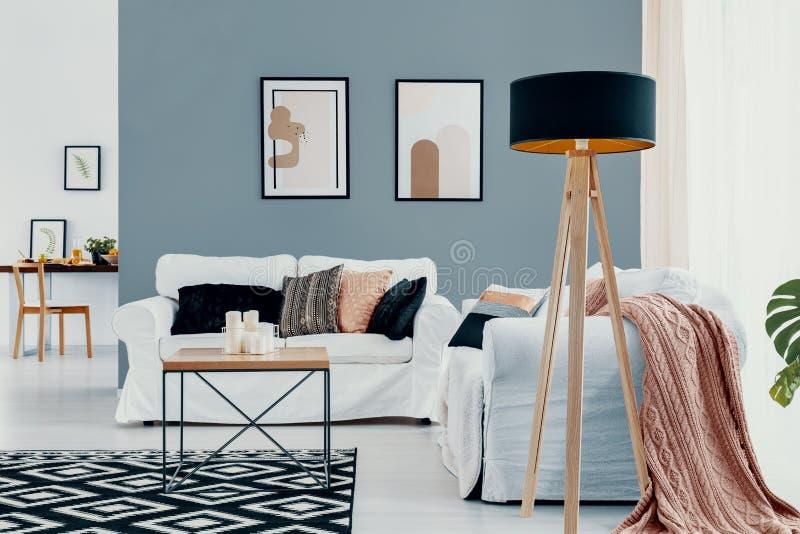 Lampa bredvid den vita soffan med rosa färgfilten i blå vardagsruminre med affischer Verkligt foto royaltyfria foton