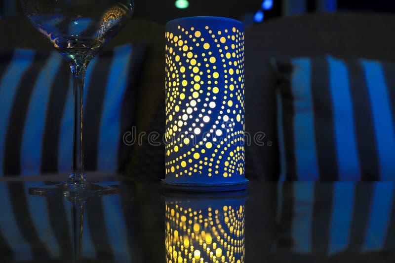 Lampa na wakacyjnym stole w wieczór gościu restauracji Elegancki błękitny lampion z żółtą świeczką na szklanym stole i szkle przy obraz stock