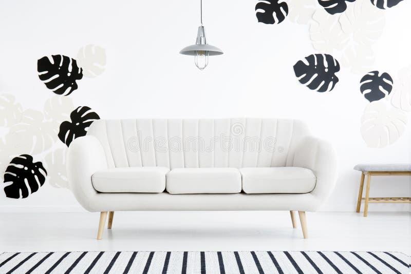 Lampa nad kanapa w białym żywym izbowym wnętrzu z pasiastym carpe obraz royalty free