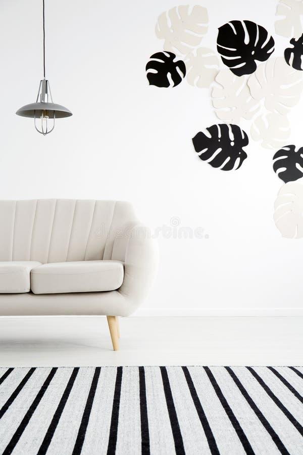 Lampa nad leżanka w białym żywym izbowym wnętrzu z monstera lea obrazy stock