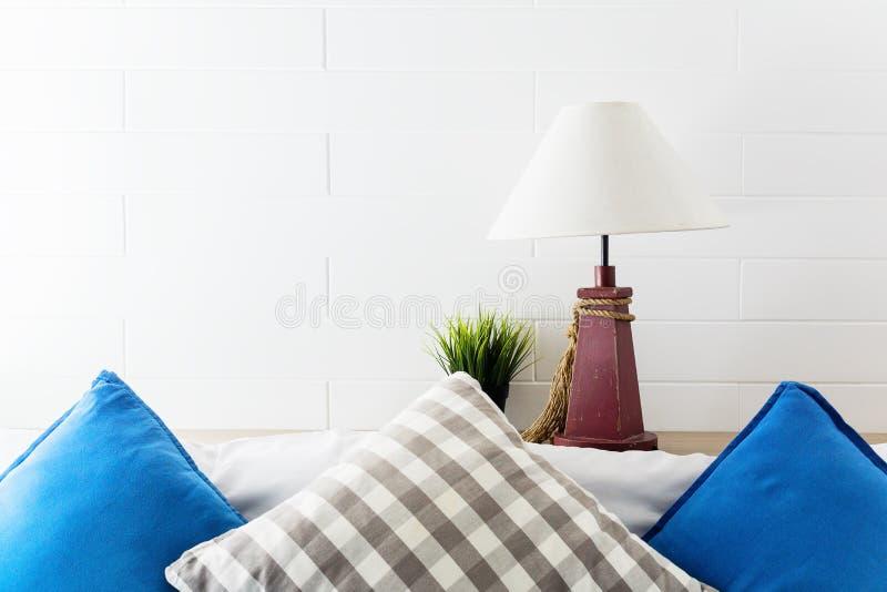 Lampa och grön växt på sängkant med blåa och gråa pollows Inre bakgrund för hotellrum fotografering för bildbyråer