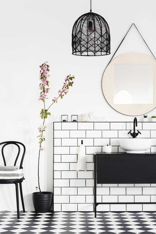 Lampa och spegel ovanför den svarta handfatet i modern badruminre med växten och stol Verkligt foto royaltyfri foto