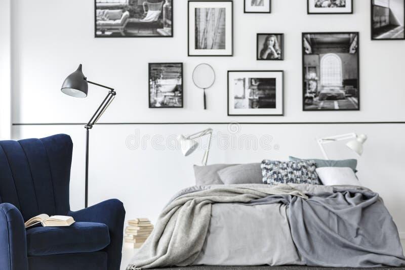 Lampada accanto alla poltrona nell'interno bianco della camera da letto con la galleria sopra il letto con gli strati Foto reale fotografie stock