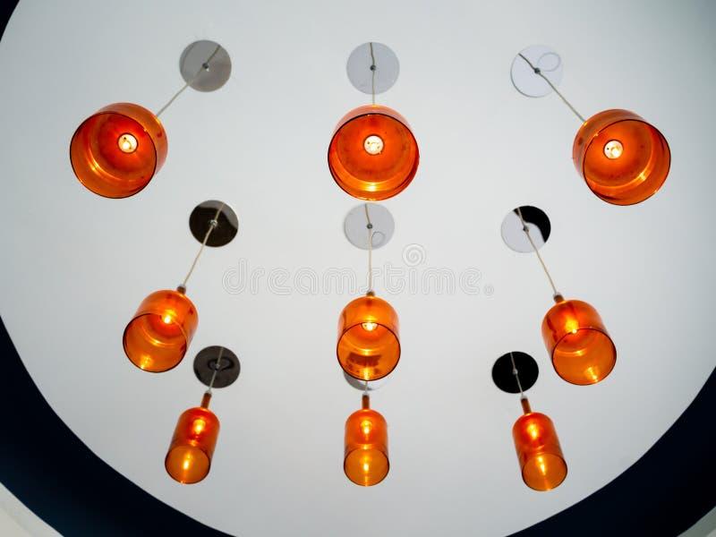 Lampada arancio moderna del soffitto che pende dal soffitto bianco Accensione del concetto della decorazione immagine stock