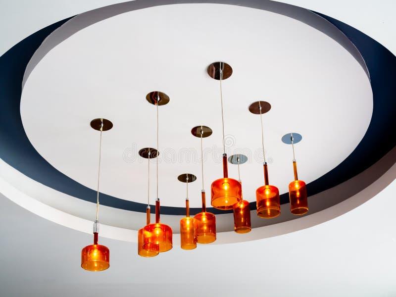 Lampada arancio moderna del soffitto che pende dal soffitto bianco Accensione del concetto della decorazione immagini stock libere da diritti