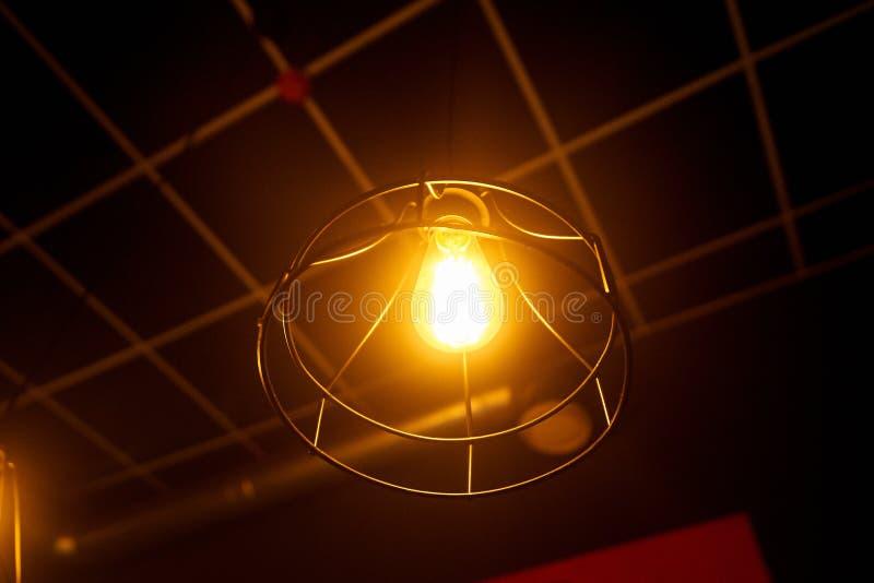 lampada arancio nel telaio d'acciaio rotondo che appende sul soffitto fotografia stock