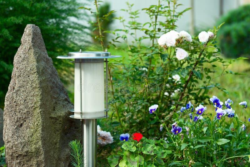 Lampada autoalimentata solare sul fondo del giardino fotografia stock