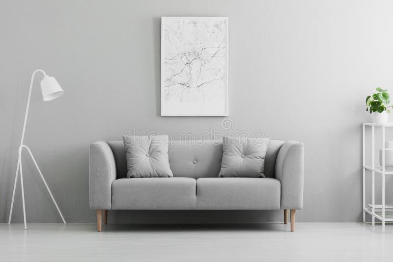 Lampada bianca accanto allo strato grigio nei wi interni del salone minimo fotografie stock libere da diritti