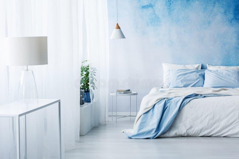 Lampada bianca su una tavola nell'interno blu luminoso della camera da letto con il letto a immagine stock libera da diritti