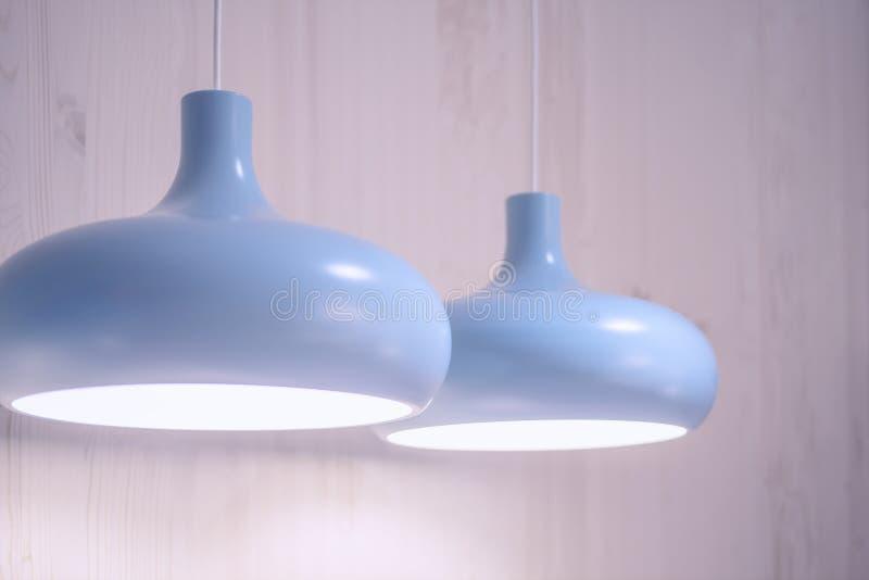 Lampada blu che appende sul cavo bianco sul fondo della parete fotografia stock