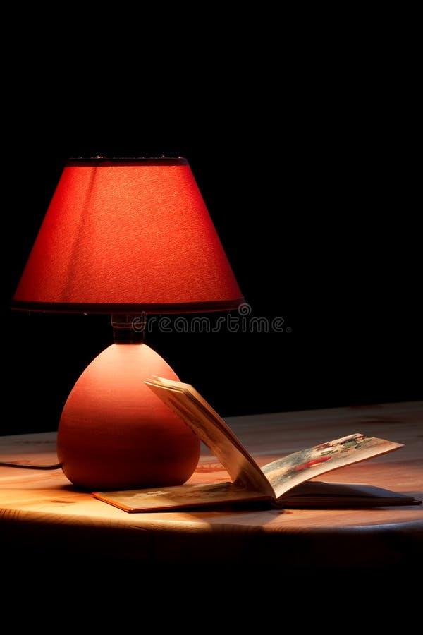 Lampada che illumina un libro fotografie stock