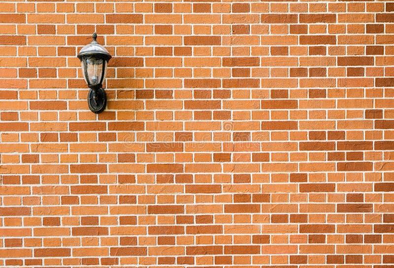 Lampada da parete d'annata su un muro di mattoni decorativo rosso-arancio e marrone fotografia stock libera da diritti
