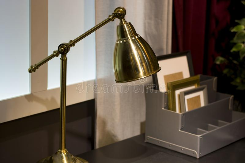 Lampada da tavolo dorata sulla parete della casa della casa di comodità della tenda della tavola fotografie stock